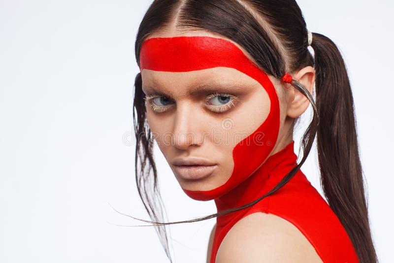 Stående av en utöver det vanliga modell med idérik makeup och hår Studiofotoperiod arkivfoton