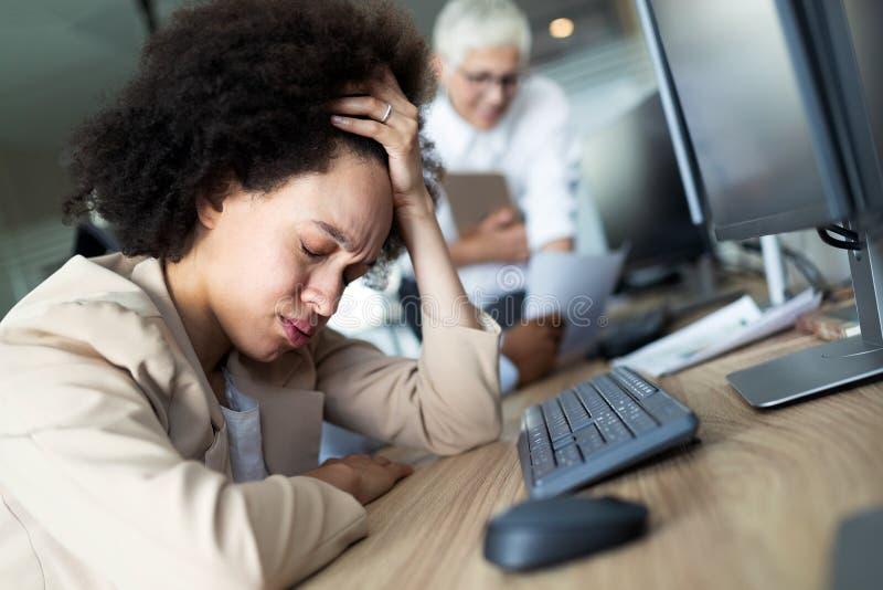 Stående av en utmattad affärskvinna som sover på arbete royaltyfri fotografi