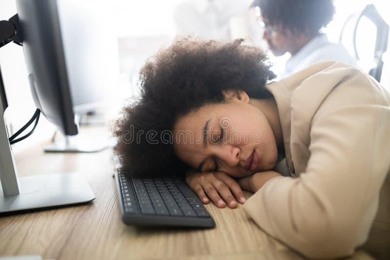 Stående av en utmattad affärskvinna som sover på arbete royaltyfri foto