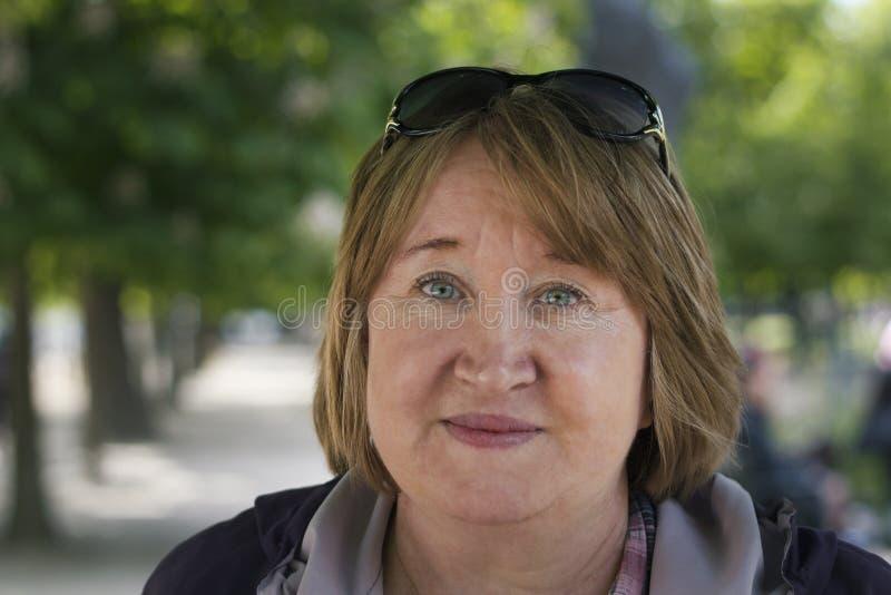 Stående av en utomhus- le äldre kvinna arkivfoto