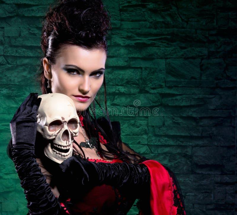 Stående av en vampyrlady som rymmer en mänsklig skalle royaltyfria foton