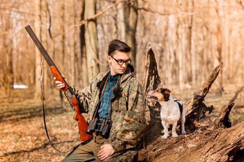 Stående av en yang jägare med en hund på skogen arkivfoto