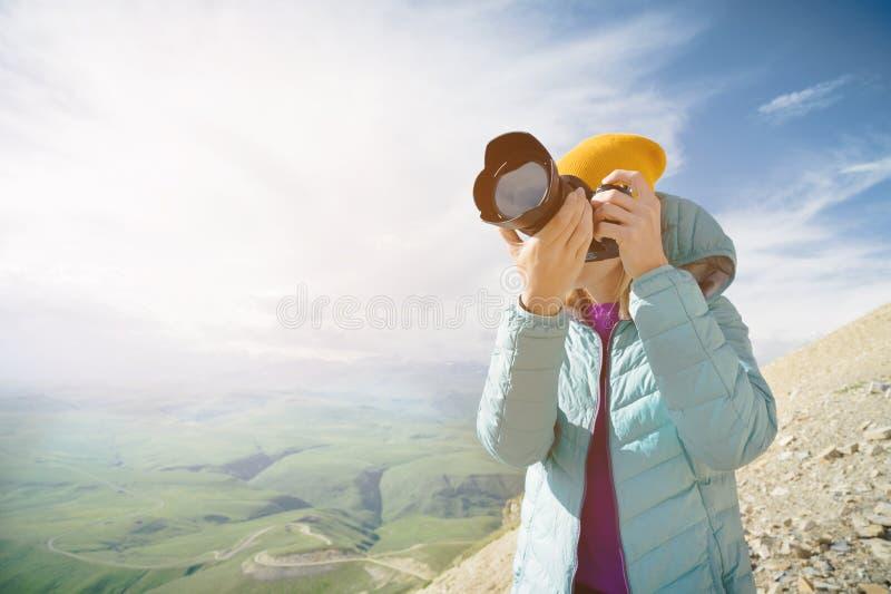 Stående av en yrkesmässig fotograf i den öppna luften En flickafotograf tar bilder av hennes kamera på hennes kamera royaltyfri bild