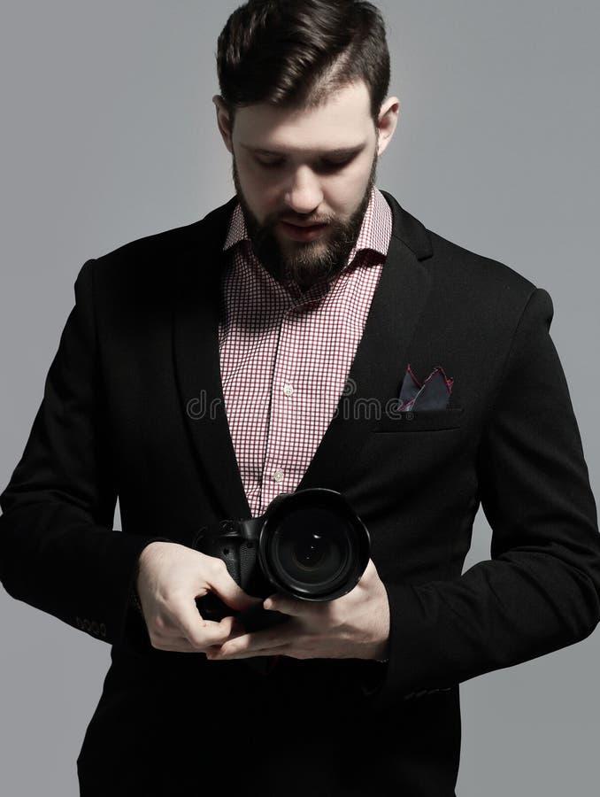 Stående av en yrkesmässig fotograf i en dräkt med en kamera royaltyfri fotografi