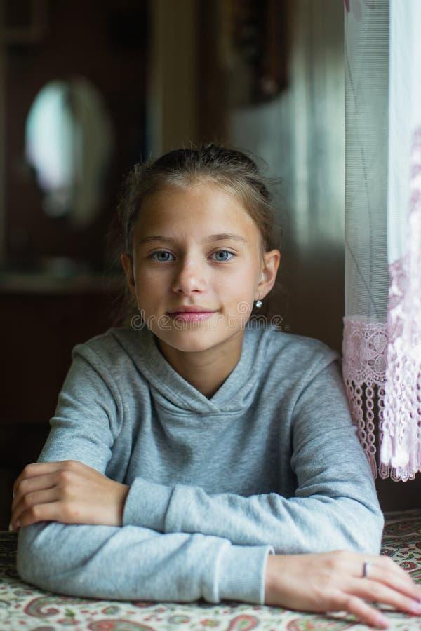 Stående av engammal flicka som sitter på tabellen royaltyfria bilder