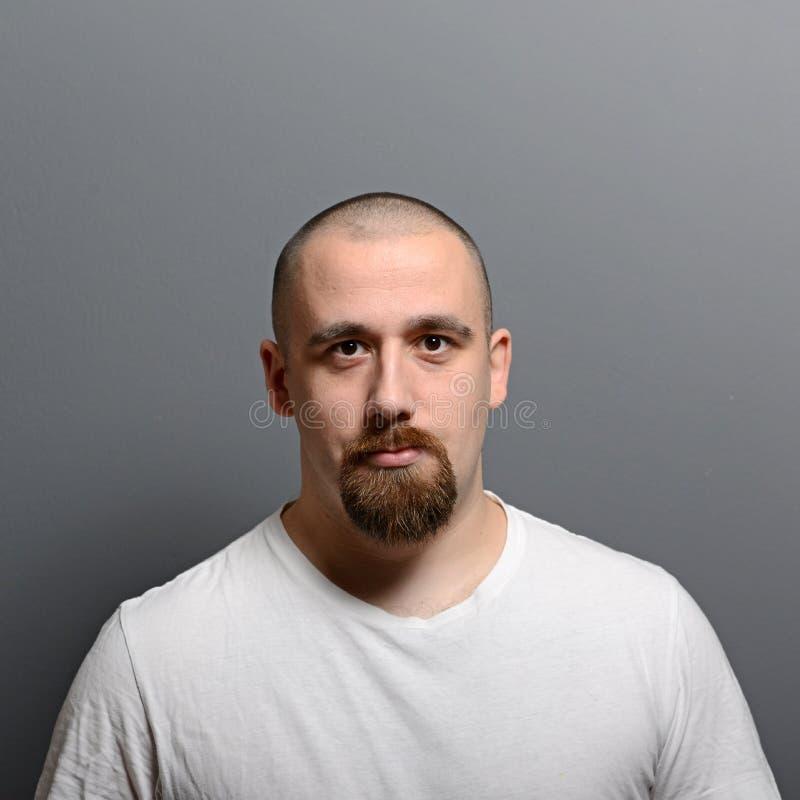 Stående av ett anseende för ung man mot grå bakgrund arkivfoto