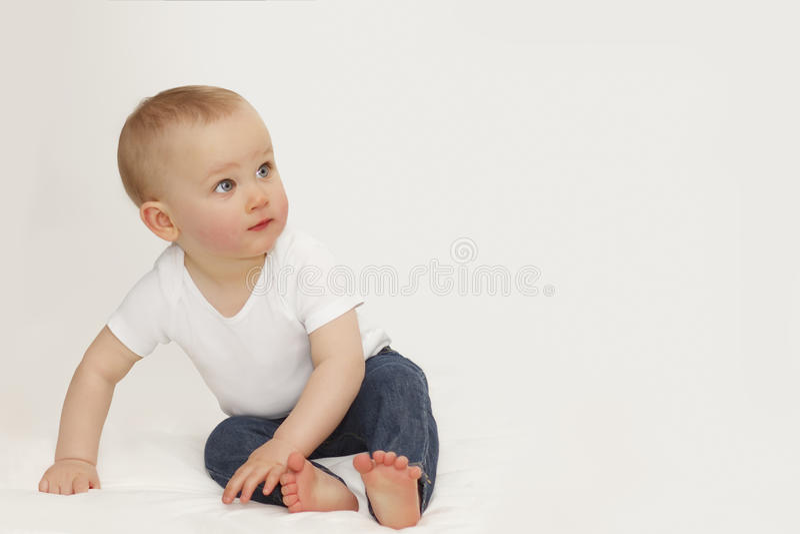 Stående av ett barn med blåa ögon på en grå bakgrund i jeans och en vit T-tröja arkivfoton
