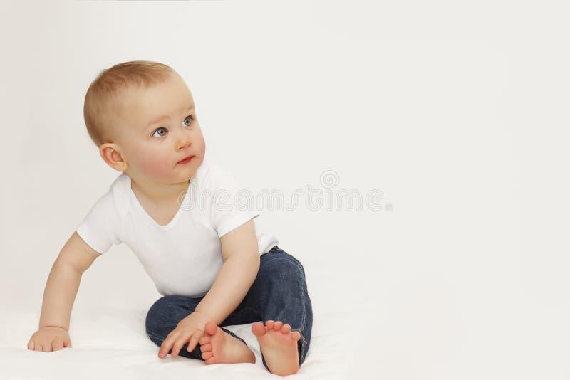 Stående av ett barn med blåa ögon på en grå bakgrund i jeans och en vit T-tröja royaltyfria foton