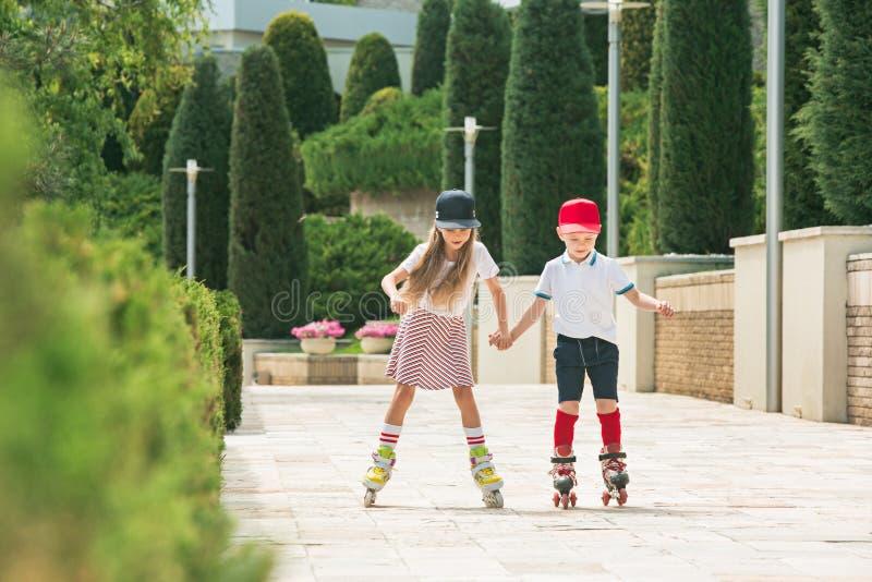 Stående av ett charmigt tonårs- par som tillsammans åker rullskridskor arkivfoton