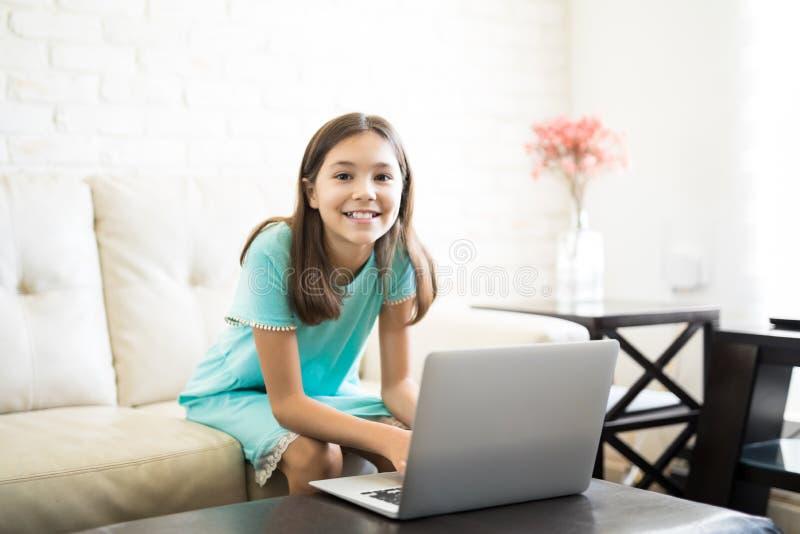 Stående av ett flickabarn som hemma sitter genom att använda bärbara datorn royaltyfri fotografi