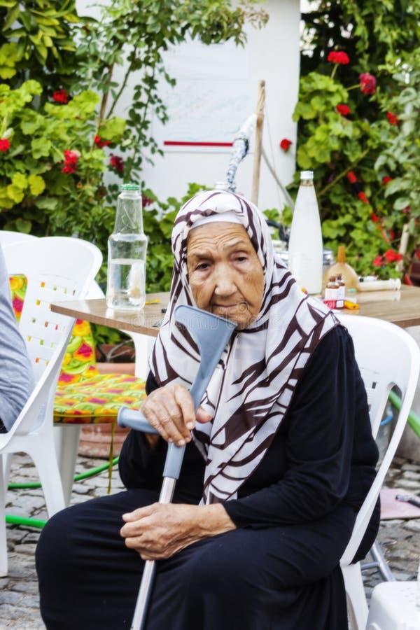 Stående av ett gammalt sammanträde för rörelsehindrad kvinna på gatan royaltyfria foton