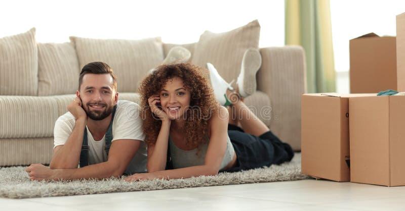 Stående av ett gift par som ligger på golvet, når att ha flyttat sig fotografering för bildbyråer