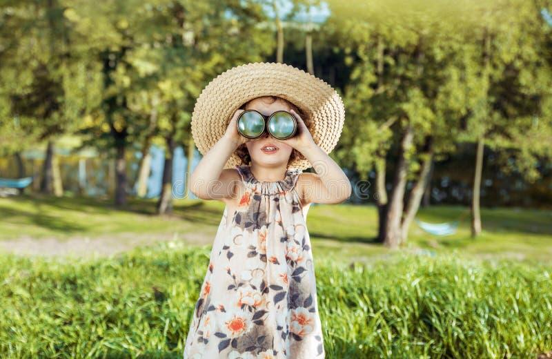 Stående av ett gladlynt, liten flicka som ser till och med binoculaen royaltyfri foto