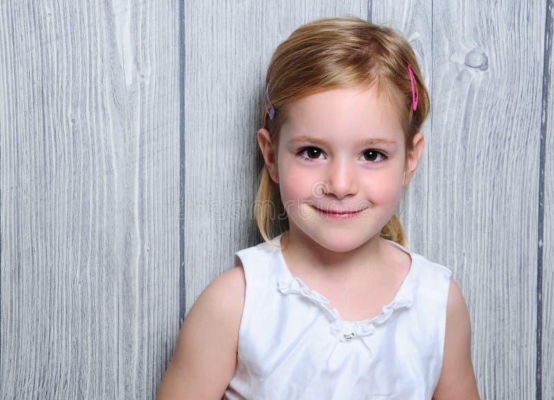 Stående av ett gulligt fyra-år som ler den blonda flickan i den vita klänningen och färgrika hårspännar i hennes hår royaltyfria foton