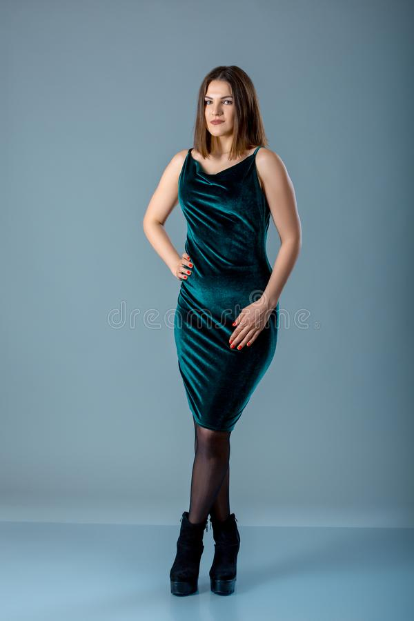 Stående av ett härligt fullt eller plus formatflicka i en grön klänning på en grå bakgrund arkivbild
