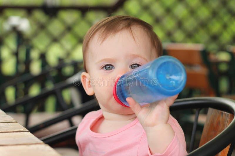 stående av ett härligt gulligt rödhårig manbarn som sitter på en tabell i ett kafé och ett dricksvatten från en plast- flaska fotografering för bildbyråer
