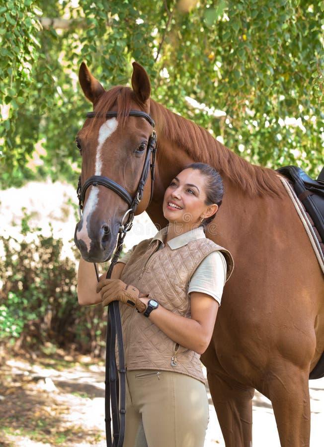 Stående av ett härligt skicklig ryttarinnaanseende med hästen utomhus royaltyfria foton