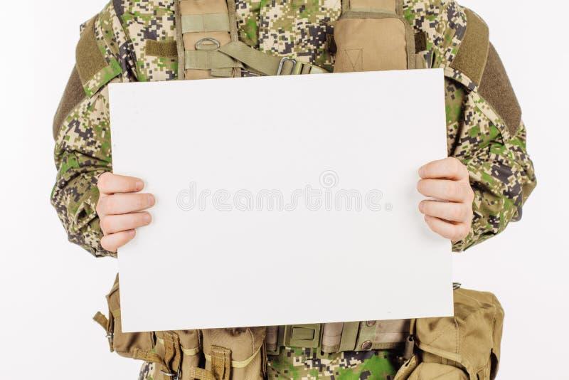 Stående av ett hållande vitt ark för soldat av papper mot vit royaltyfria bilder