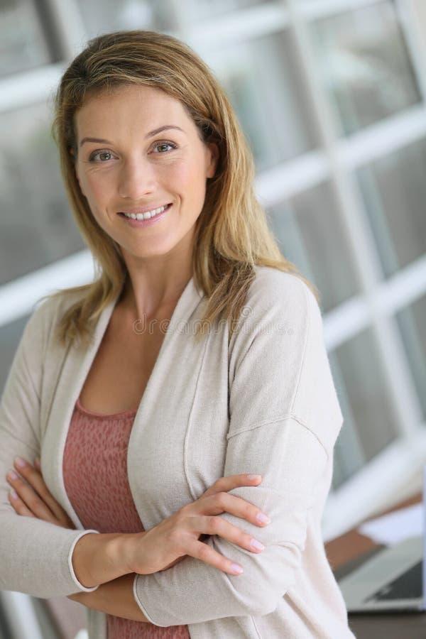 Stående av ett lyckat härligt blont kvinnaanseende på hennes kontor royaltyfria foton