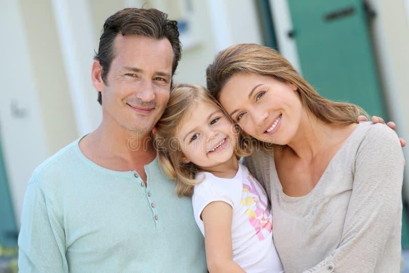 Stående av ett lyckligt familjanseende på framdel av deras nya hus royaltyfria foton