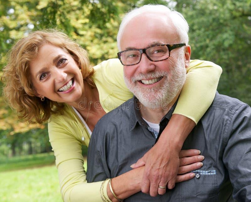 Stående av ett lyckligt högt par som utomhus ler arkivfoto