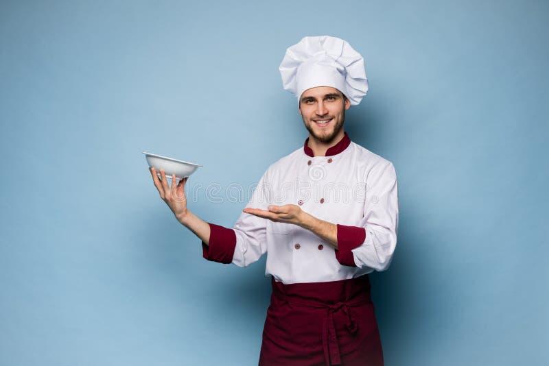 Stående av ett lyckligt manligt kockkockanseende med plattan som isoleras på ljust - blå bakgrund arkivbild
