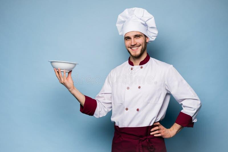 Stående av ett lyckligt manligt kockkockanseende med plattan som isoleras på ljust - blå bakgrund royaltyfria foton