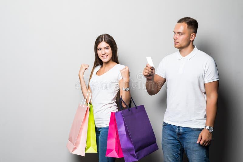 Stående av ett lyckligt par med en shoppa påse med ett kort och att se kameran på vit bakgrund royaltyfria foton