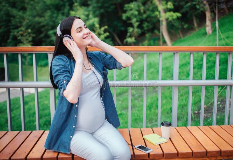 Stående av ett lyckligt svart hår och en stolt gravid kvinna i en stad i bakgrunden Hon sitter på en stadsbänk arkivbilder