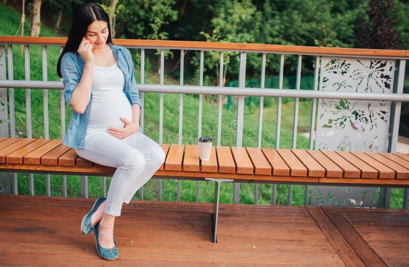 Stående av ett lyckligt svart hår och en stolt gravid kvinna i en stad i bakgrunden Närbildbild av den kvinnliga modellen royaltyfria bilder