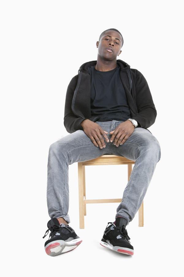 Stående av ett moderiktigt afrikansk amerikanmansammanträde på stol över grå bakgrund arkivfoton