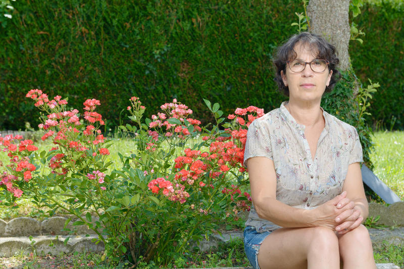 Stående av ett moget kvinnasammanträde i trädgård arkivfoto