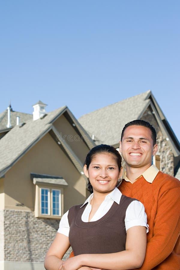 Stående av ett par förutom ett hus royaltyfria foton