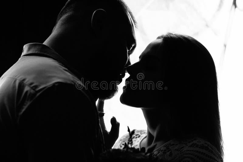 Stående av ett romantiskt par i en bakgrundsbelysning från ett fönster eller en dörr, en silhuett av ett par i en dörr med bakgru royaltyfri foto