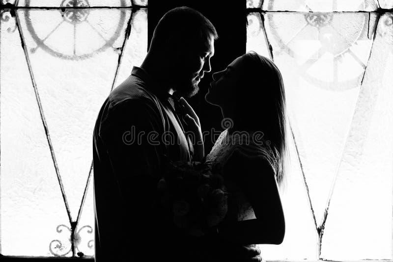 Stående av ett romantiskt par i en bakgrundsbelysning från ett fönster eller en dörr, en silhuett av ett par i en dörr med bakgru royaltyfri bild