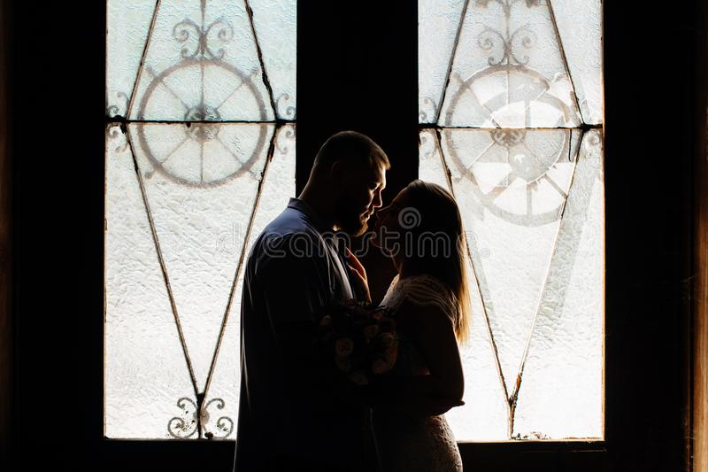 Stående av ett romantiskt par i ett panelljus från ett fönster eller en dörr, kontur av ett par i en dörröppning med ett panellju arkivfoto