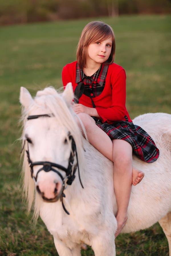 Stående av ett sammanträde för behandla som ett barnflicka på en vit ponny royaltyfria foton
