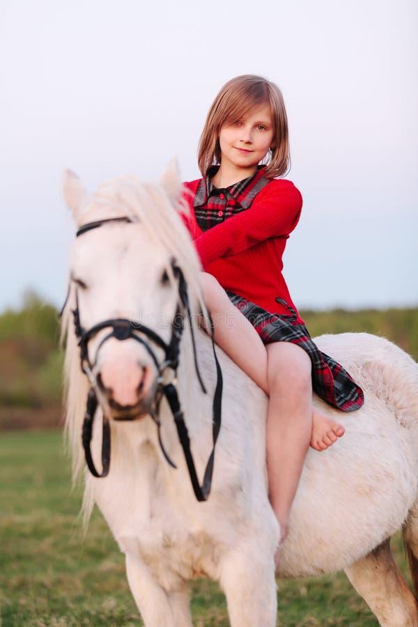 Stående av ett sammanträde för behandla som ett barnflicka på en vit ponny arkivfoton