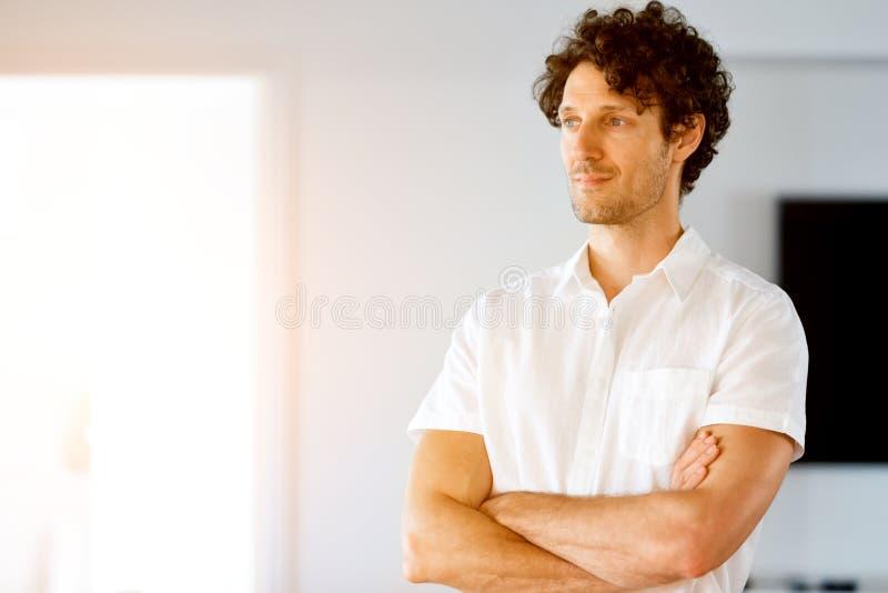 Stående av ett smart anseende för ung man i kök royaltyfri foto