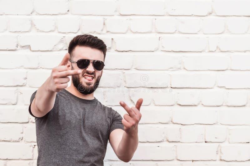 Stående av ett stiligt anseende för ung man mot en vit tegelstenvägg Leende oanständiga gester arkivbilder