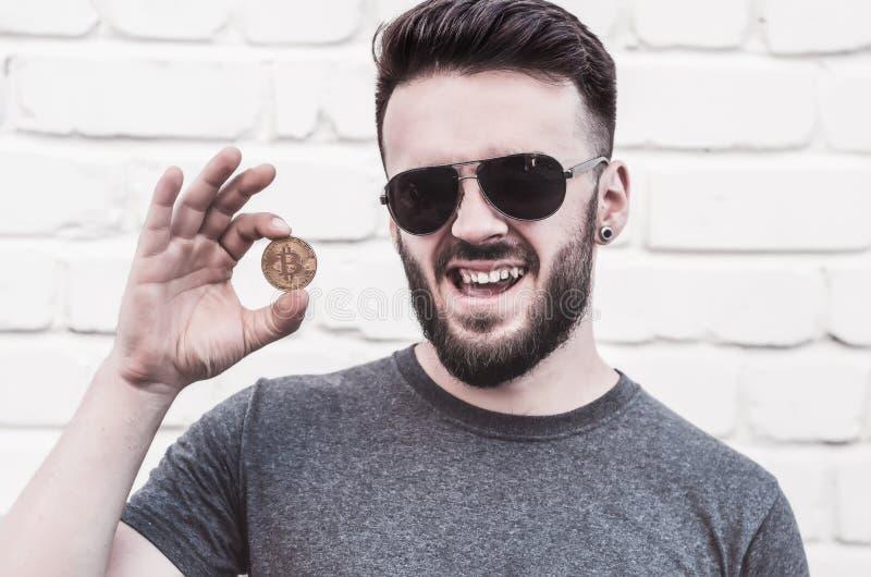 Stående av ett stiligt anseende för ung man mot en vit tegelstenvägg Leende oanständiga gester Rymmer en bitcoin i hans hand arkivfoton