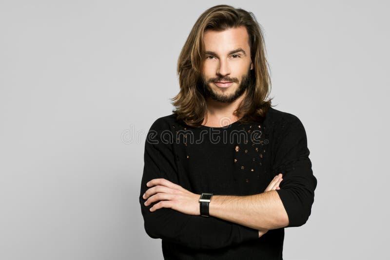 Stående av ett stiligt le mananseende med hans armcrosse royaltyfri bild