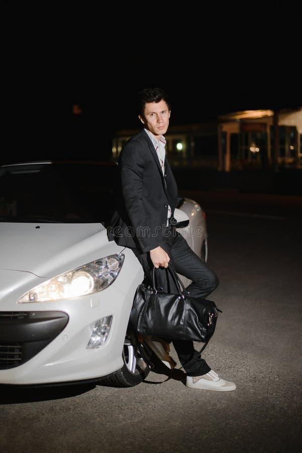 Stående av ett stiligt mananseende bredvid hans vita cabriolet uteliv Affärsman i dräkt i lyxig bil fotografering för bildbyråer