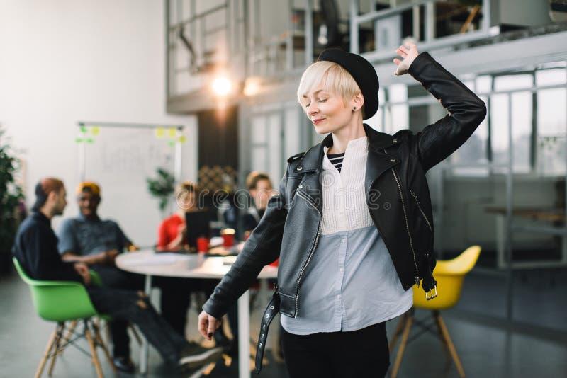 Stående av ett tillfälligt kvinnligt anseende för kontorsarbetare med armar upp och ner och att ha gyckel på ett ljust kontor, me royaltyfri foto