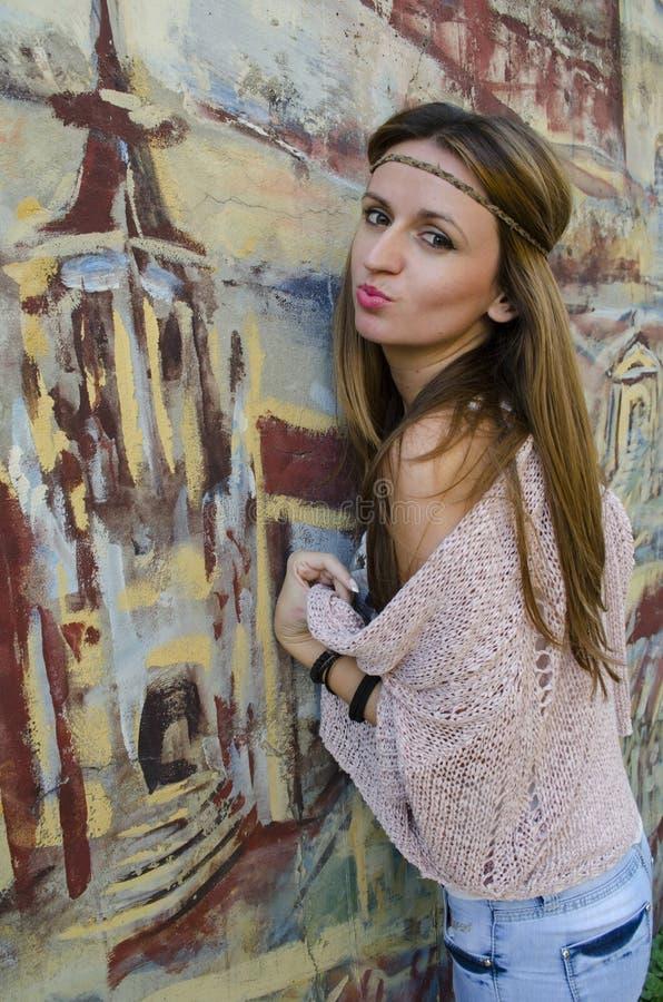 Stående av ett ung flickaanseende vid väggen med en målad grafit arkivbild