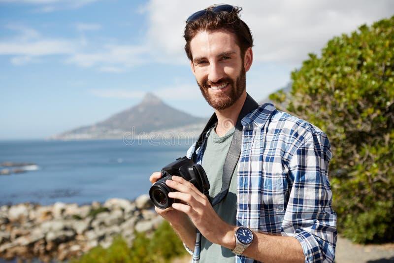 Stående av ett ungt attraktivt mananseende nära havet med arkivfoton