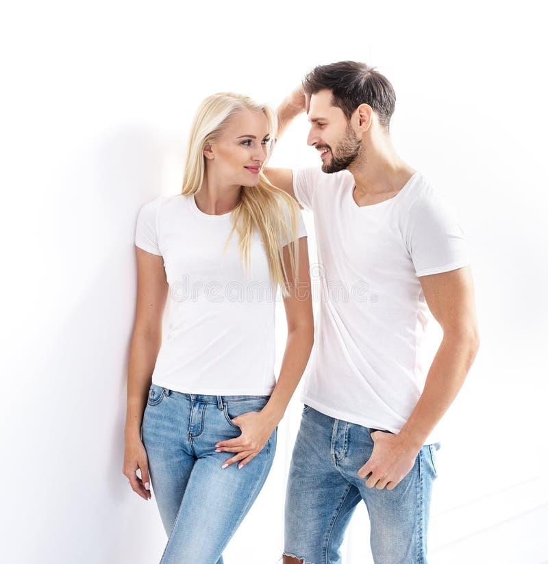 St?ende av ett ungt attraktivt par som b?r tillf?llig kl?der arkivbild