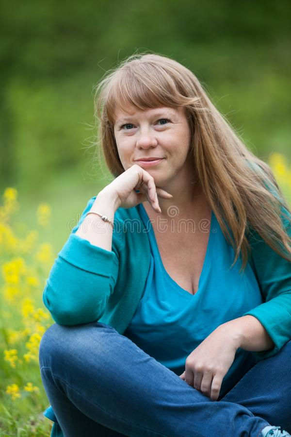 Stående av ett ungt Caucasian kvinnasammanträde i ett fält, blondish långt hår arkivfoton