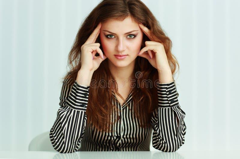 Stående av ett ungt eftertänksamt affärskvinnasammanträde på tabellen royaltyfri fotografi