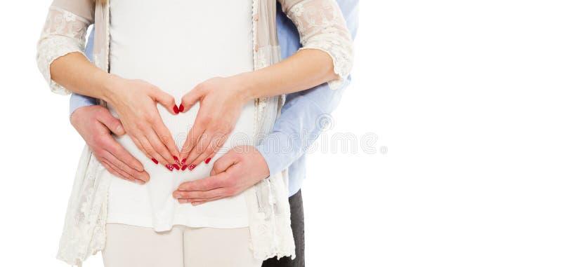 Stående av ett ungt gravid par på en vit bakgrundsshow förälskelsetecknet royaltyfri foto